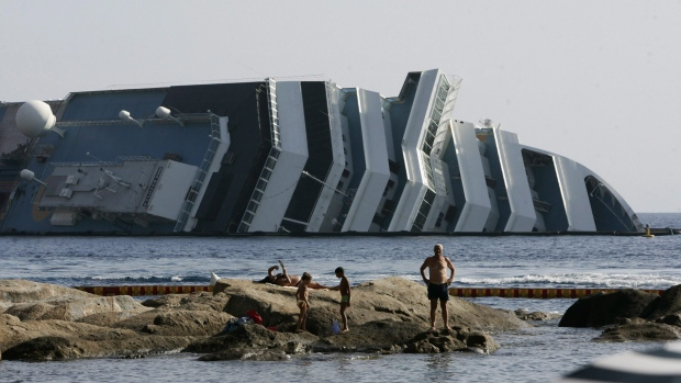 In this July 12, 2012 file photo tourists relax on rocks in front of the Costa Concordia wreckage on the Giglio Island, Italy. (AP Photo/Gregorio Borgia, file)