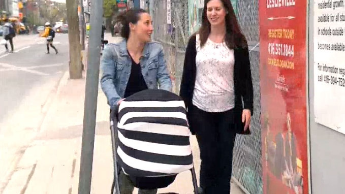 Residents of Leslieville are seen walking in the area with a stroller.