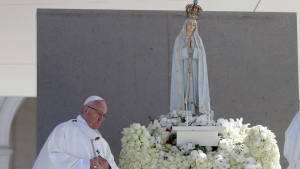 Pope Francis walks past a statue of the Virgin Mary prior to the start of a mass at the Sanctuary of Our Lady of Fatima Saturday, May 13, 2017, in Fatima, Portugal. (AP Photo/Alessandra Tarantino)