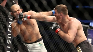 Stipe Miocic, lands a right against Junior Dos Santos in a mixed martial arts bout at UFC 211 for the UFC heavyweight championship, Saturday, May 13, 2017, in Dallas. (AP Photo/Gregory Payan)