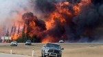In this May 7, 2016 file photo, a wildfire burns south of Fort McMurray, Alberta. (Jonathan Hayward /The Canadian Press via AP, File)