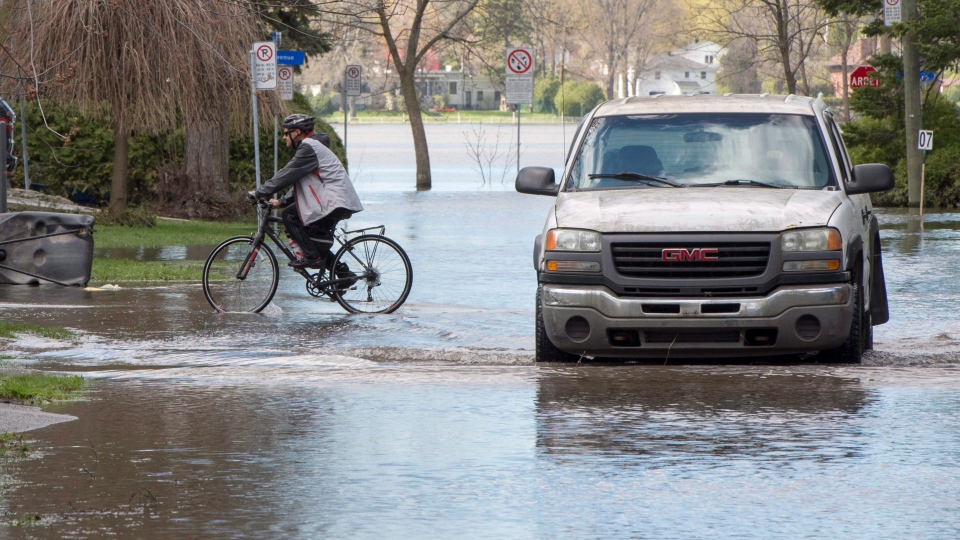 Residents make their way through a flooded street as the water starts to recede Friday, May 12, 2017 in Laval, Quebec. THE CANADIAN PRESS/Ryan Remiorz