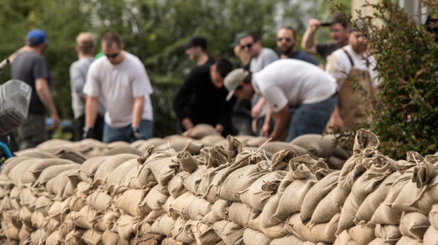Volunteers help out with sandbagging at a house along Marshall St. that backs onto Mill Creek in Kelowna, B.C. on Friday, May 12, 2017. THE CANADIAN PRESS/Jeff Bassett