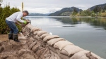 Malcolm Uttley places sandbags along a small canal between Kalamalka Lake and Wood Lake at the Tween Lake Resort in Oyama B.C. just north of the City of Kelowna on Friday, May 12, 2017. Thunderstorms and heavy rain bypassed British Columbia's Okanagan region Thursday night, sparing the flood-plagued region from further high water, but emergency officials said the danger has not passed. THE CANADIAN PRESS/Jeff Bassett