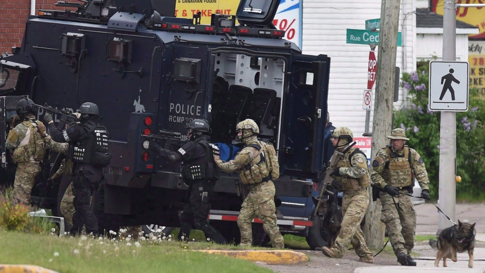 Emergency response officers enter a residence in Moncton, N.B. on Thursday, June 5, 2014. Mounties are reliving Justin Bourque's murder spree at an RCMP trial. It's alleged the RCMP failed to provide members and supervisors with the appropriate information, instruction and training in an active-shooter event, and didn't give members the appropriate equipment. (THE CANADIAN PRESS/Andrew Vaughan)