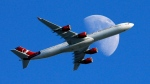 In this Sunday, Aug. 23, 2015, file photo, a Virgin Atlantic passenger plane crosses a waxing gibbous moon on its way to the Los Angeles International Airport, in Whittier, Calif. (AP Photo/Nick Ut, File)