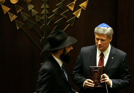 Prime Minister Stephen Harper holds a prayer book given to him by Rabbi Mendel Kaplan, left, during the grand opening of the Ernest Manson Lubavitch Centre in Thornhill, Ontario on Thursday, March 26, 2009. (THE CANADIAN PRESS / Darren Calabrese)