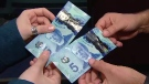 A counterfeit $5 bill, above, is shown with a real one. The holograms on the fake one have been replaced with foil, and tape has been substituted for the clear plastic panel.
