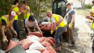 Residents and volunteers pile leftover sandbags into a loader for transportation to the curb in Cumberland, Ont. after flood waters devastated their community in May 2017.(CTV Ottawa)