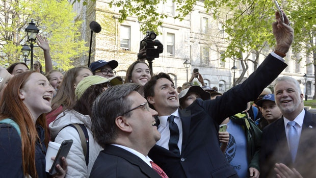 The Prime Minister Justin Trudeau stops for selfies as Premier of Quebec Philippe Couillard and Mayor Coderre as look as they walk to the Notre-Dame Basilica to attend a mass marking the 375th anniversary of the founding of Montreal on Wednesday May 17, 2017. THE CANADIAN PRESS/Paul Chiasson