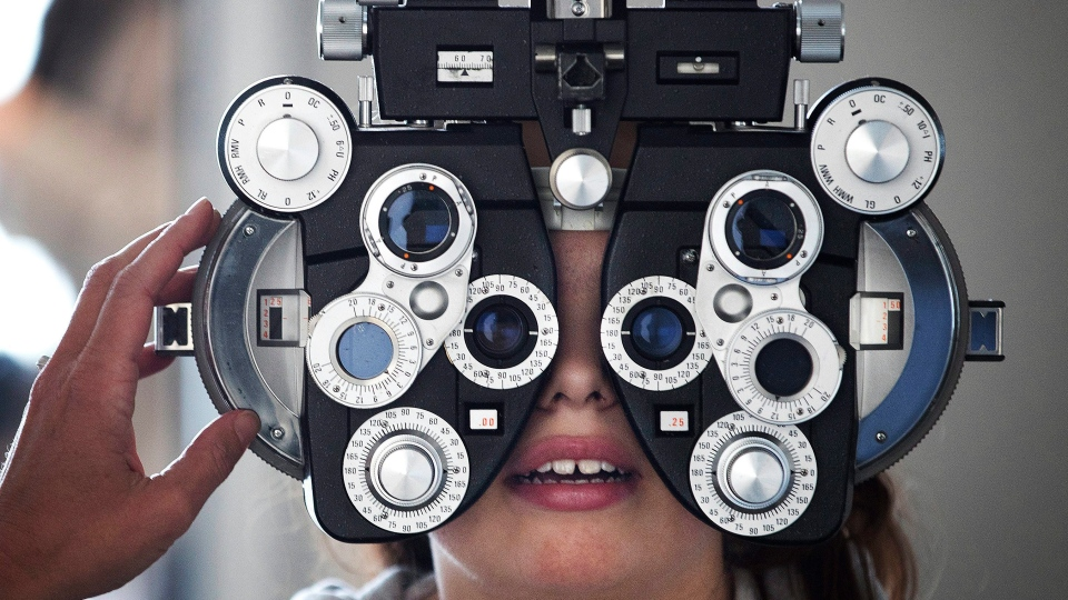In this Tuesday, March 21, 2017, photo, Optometrist Linda Morgan uses a phoropter to help determine a prescription for Liberty Elementary School student Brooklyn Richotte during a vision screening in Omaha, Neb. (Megan Farmer/Omaha World-Herald via AP)