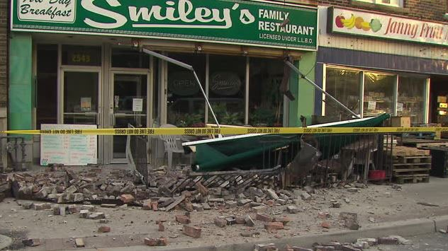 Several bricks broke off the roof of a family restaurant in Danforth Village, slamming into an awning and pedestrian when they hit the sidewalk. (CTV News Toronto)
