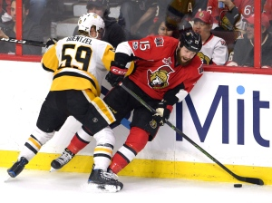 Ottawa Senators centre Zack Smith (15) plays the puck as he's hit against the boards by Pittsburgh Penguins centre Jake Guentzel (59) during the third period of game three of the Eastern Conference final in the NHL Stanley Cup hockey playoffs in Ottawa on Wednesday, May 17, 2017. (Adrian Wyld / THE CANADIAN PRESS)