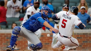 Atlanta Braves' Freddie Freeman (5) scores on a Nick Markakis two-run base hit as the ball gets away from Toronto Blue Jays catcher Luke Maile (22) in the first inning of a baseball game, Wednesday, May 17, 2017, in Atlanta. (AP Photo/John Bazemore)