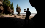 A tourist stops to take a photo of the Hopewell Rocks on the Bay of Fundy, N.B., Friday, August, 16, 2013. (Jonathan Hayward / THE CANADIAN PRESS)