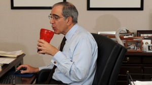 Peter V. Handal sips a soda and snacks on mixed nuts while working at his desk during lunch, in Hauppauge, N.Y., on Thursday, April 2, 2009. (AP Photo/John Dunn)