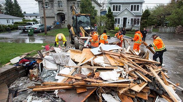 City workers pick up debris from removed from a flooded house in the Pierrefonds borough of Montreal Sunday, May 14, 2017. THE CANADIAN PRESS/Paul Chiasson