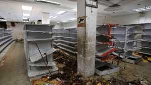 Destroyed merchandise is strewn on a supermarket floor around empty shelves, a day after a night of looting in El Valle neighborhood in Caracas, Venezuela, Friday, April 21, 2017. (AP Photo/Fernando Llano)