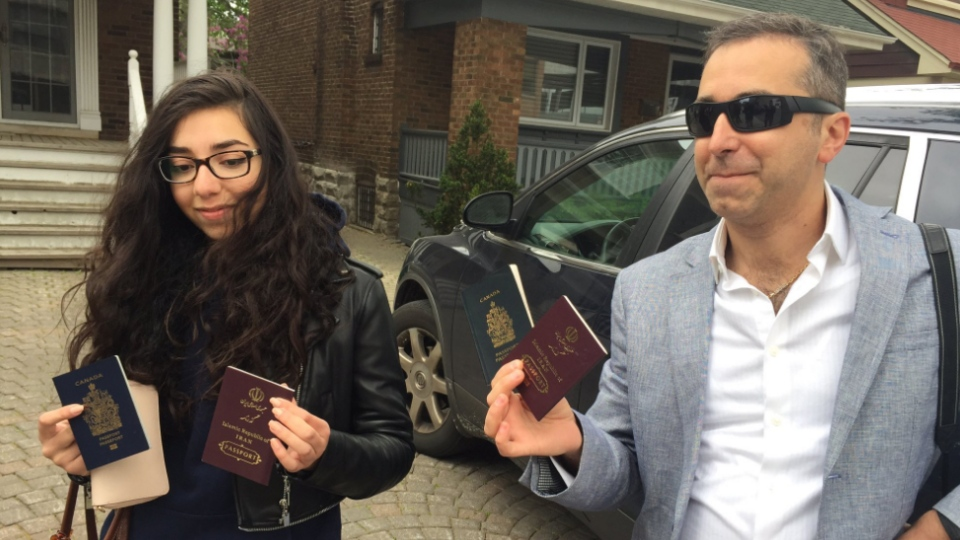 Two Iranian-Canadians show off their passports. They were among many others who headed to the U.S. to vote in Iran's presidential election on Friday, May 19, 2017. (Twitter: PeterAkman)