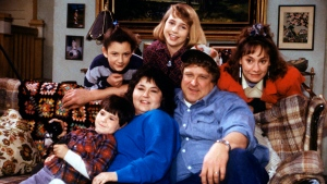 In this undated image released by ABC, shows the cast members of 'Roseanne,' Michael Fishman as DJ Conner, seated from left, Roseanne Barr as Roseanne Barr, John Goodman as Dan Conner, and second row from left, Sara Gilbert as Darlene Conner, Alicia Goranson as Becky Conner and Laurie Metcalf as Jackie Harris. (Dan Watson / ABC via AP)