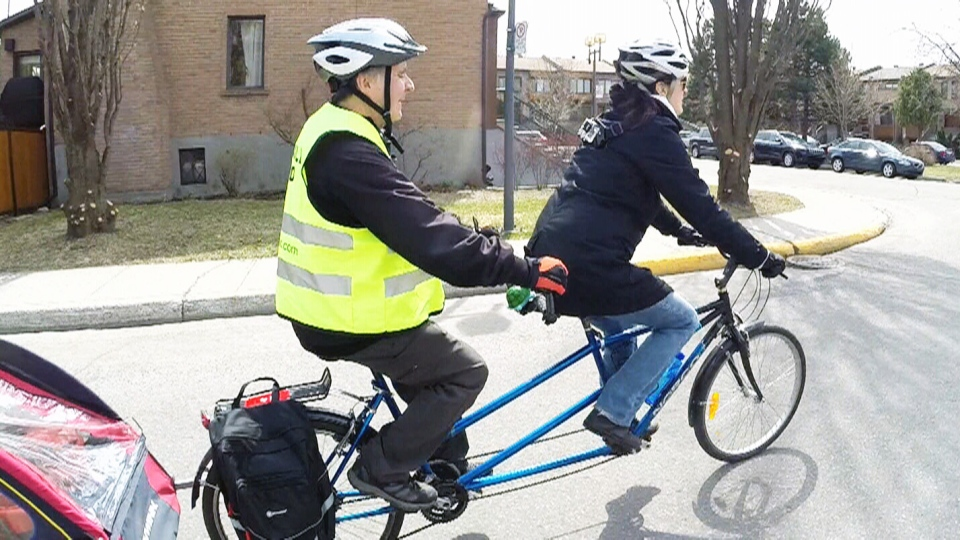 Meals-on-Wheels volunteers Andre Beaudoin and Anick Bergeron ride a tandem bike in Montreal on Friday, May 19, 2017.