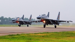 In this undated file photo released Saturday, Aug. 6, 2016, by China's Xinhua News Agency, two Chinese SU-30 fighter jets take off from an unspecified location to fly a patrol over the South China Sea. (Jin Danhua/Xinhua via AP)