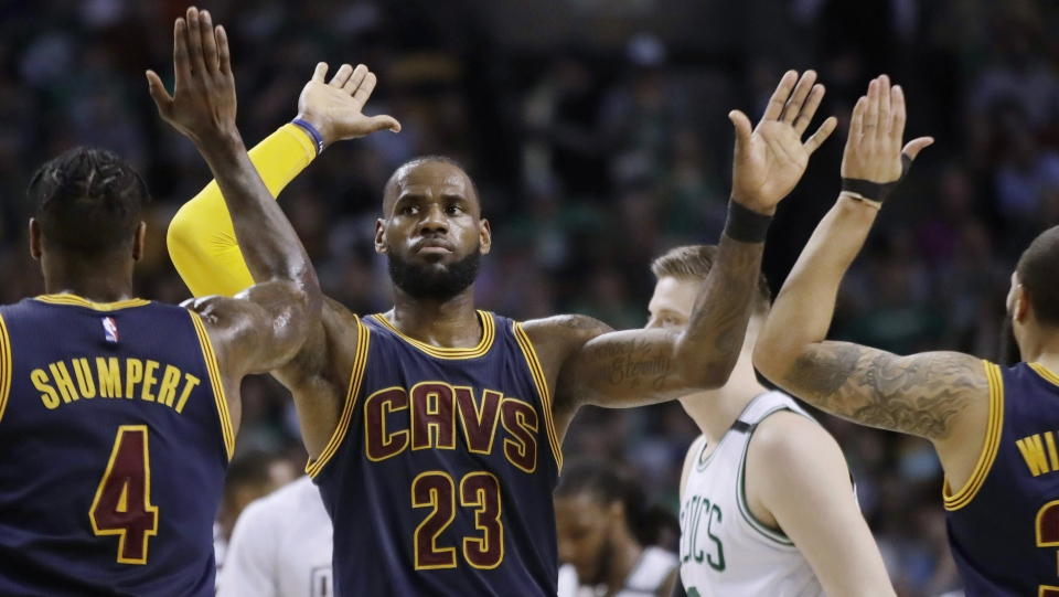 Cleveland Cavaliers forward LeBron James trades high-fives with teammates Iman Shumpert, left, and Deron Williams, right, during the first half of Game 2 of the NBA basketball Eastern Conference finals against the Boston Celtics, Friday, May 19, 2017, in Boston. (AP / Elise Amendola)