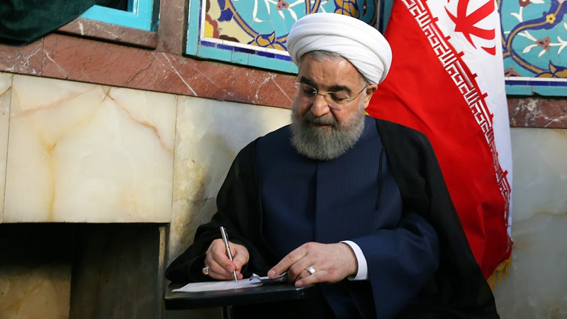 Iranian President Hassan Rouhani fills in his ballot while voting for the presidential and municipal councils election at a polling station in Tehran, Iran, Friday, May 19, 2017.  (Iranian Presidency Office via AP)
