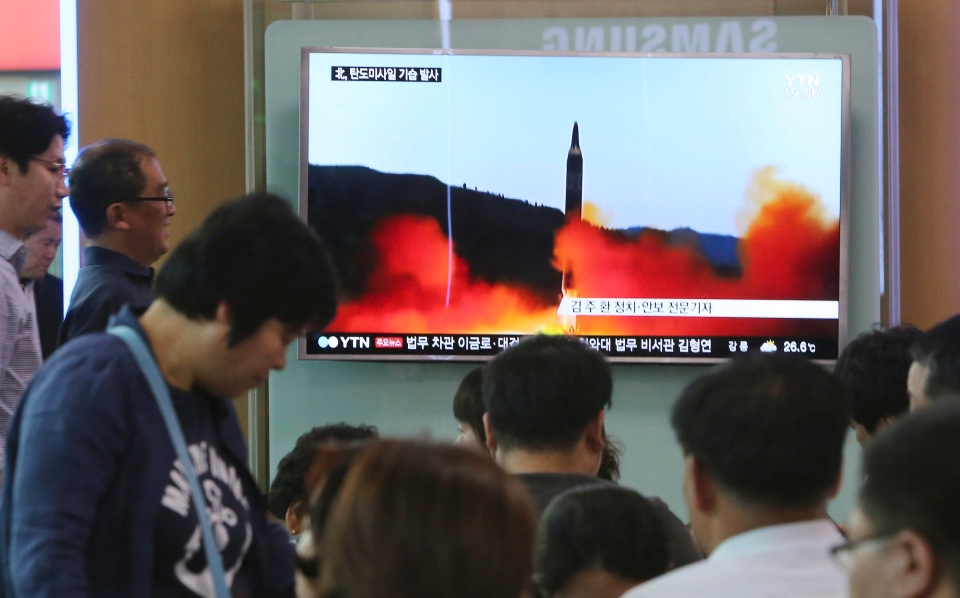 People watch a TV news program showing a file image of a missile launch by North Korea, at the Seoul Railway Station in Seoul, South Korea, Sunday, May 21, 2017. (AP / Ahn Young-joon)