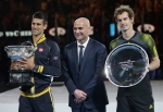 In this file photo, Serbia's Novak Djokovic, left, holds a trophy as he stands next to former champion Andre Agassi in Melbourne, Australia, Sunday, Jan. 27, 2013. (AP / Dita Alangkara)