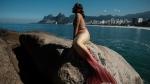 Davi de Oliveira Moreira, known as Sereio (merman in Portuguese), poses in his mermaid tail costume at Arpoador Rock on Ipanema Beach in Rio de Janeiro. (YASUYOSHI CHIBA / AFP)