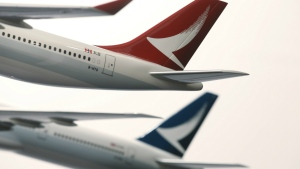 Two model jets of Hong Kong airline Cathay Dragon, formerly known as Dragonair, front, and Cathay Pacific Airways, are displayed at a news conference in Hong Kong on Jan. 28, 2016. (AP / Kin Cheung)