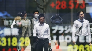 People are reflected on the electronic board of a securities firm in Tokyo on Monday, May 22, 2017. (AP / Koji Sasahara)