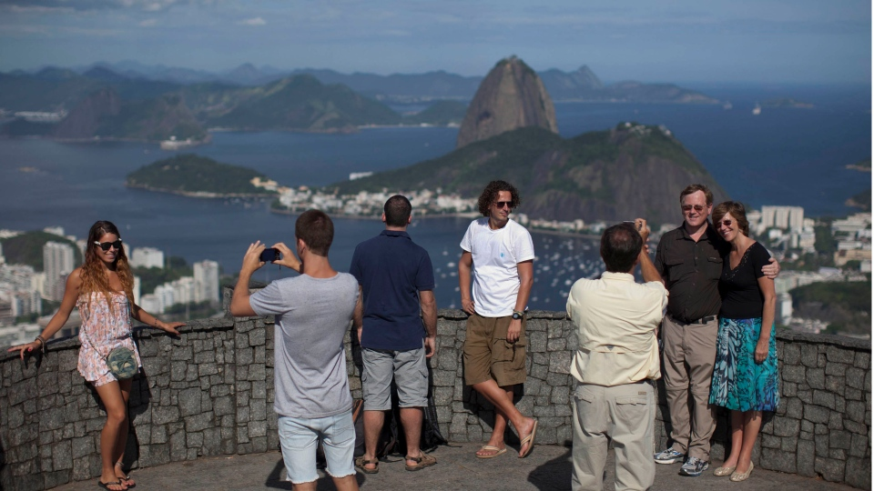 Tourists pose for a photo in front of the Sugarloaf hill in Rio de Janeiro, Brazil on Feb.14, 2012. (Felipe Dana/AP)