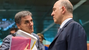 European Commissioner for the Economy Pierre Moscovici, right, talks with Greece's Finance Minister Euclid Tsakalotos prior to a meeting of Eurogroup finance ministers at the EU Council building in Brussels, Monday May 22, 2017. (AP Photo/Geert Vanden Wijngaert)