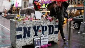 People in New York's Times Square, Monday, May 22, 2017, visit a concrete block that has become a makeshift memorial to those injured by a man who steered his car onto a sidewalk and into pedestrians for three blocks before crashing. (AP Photo/Richard Drew)