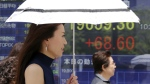 People walk by an electronic stock board of a securities firm in Tokyo on Monday, May 22, 2017. (AP / Koji Sasahara)