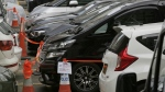 Impounded vehicles meant to be used for Uber service, centre, are parked inside the police cordon line at a police station in Hong Kong on Tuesday, May 23, 2017. (AP / Kin Cheung)