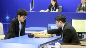 Chinese Go player Ke Jie, left, looks at the board as a person makes a move on behalf of Google's artificial intelligence program, AlphaGo, during a game of Go at the Future of Go Summit in Wuzhen in eastern China's Zhejiang Province on Tuesday, May 23, 2017. (Chinatopix)