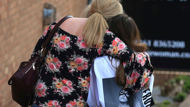 A fan is comforted as she leaves the Park Inn hotel in central Manchester, England, Tuesday May 23 2017. (AP / Rui Vieira)