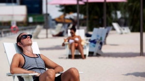 A man sun tans at Sugar Beach in Toronto on Friday, July 13, 2012. (Michelle Siu / THE CANADIAN PRESS)
