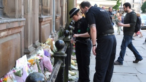 Police look at floral tributes left at St Ann's square, Manchester, England Tuesday May 23, 2017. The Islamic State group claimed responsibility Tuesday for the suicide attack at an Ariana Grande show that left more than 20 people dead as young concertgoers fled, some still wearing the American pop star's trademark kitten ears and holding pink balloons. (AP Photo/Rui Vieira)