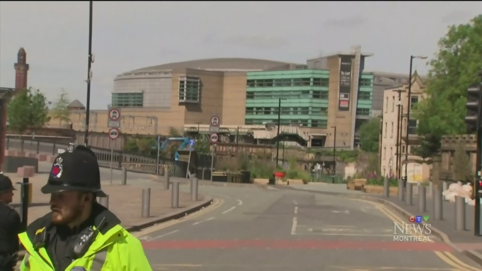 Police officers stand guard outside Manchester Arena on May 23, 2017