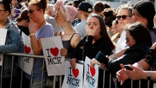 People attend a vigil in Albert Square