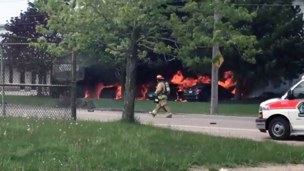 A firefighter works at the scene of a fire and fatal crash on Laird Road in Guelph. (@n8dawg44 / Twitter)
