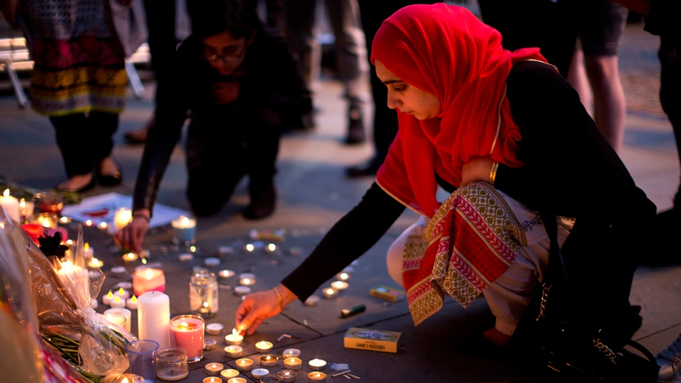 A woman lights candles after a vigil in Albert Square, Manchester, England, Tuesday May 23, 2017, the day after the suicide attack at an Ariana Grande concert that left 22 people dead as it ended on Monday night. (AP Photo/Emilio Morenatti)