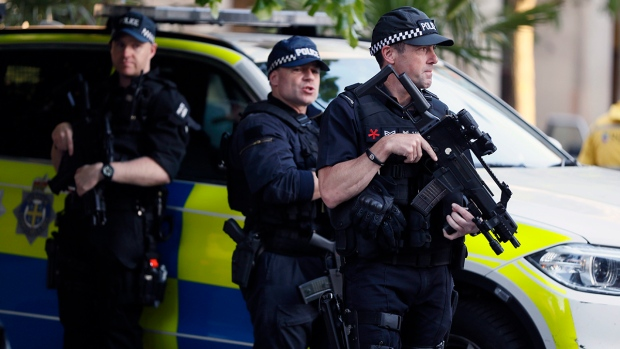 Armed police at the scene during a vigil in Albert Square, Manchester, England, Tuesday May 23, 2017, the day after the suicide attack at an Ariana Grande concert that left 22 people dead as it ended on Monday night. (AP Photo/Kirsty Wigglesworth)