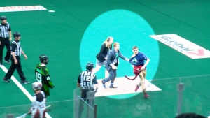 A Saskatchewan Rush fan runs from security after climbing over the plexiglass during a playoff game.