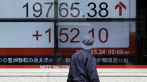 A man looks at an electronic stock board showing Japan's Nikkei 225 index at a securities firm in Tokyo on Wednesday, May 24, 2017. (AP / Eugene Hoshiko)