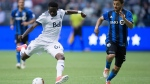 Vancouver Whitecaps' Alphonso Davies, left, takes a shot on goal as Montreal Impact's Hernan Bernardello defends during second half semifinal Canadian Championship soccer action in Vancouver, B.C., on Tuesday May 23, 2017. THE CANADIAN PRESS/Darryl Dyck